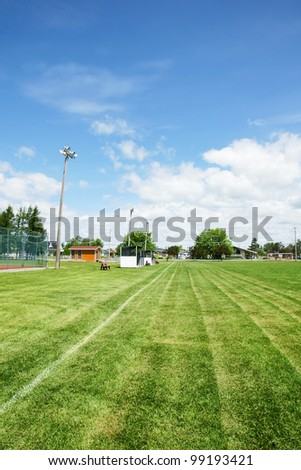 View from the corner of a soccer or football field with dug outs and lighting in a small town public recreation park.