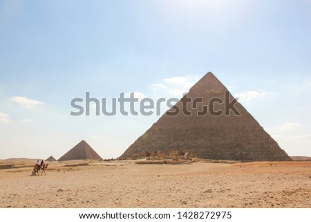 View from the desert on a series of pyramids, the three pyramids of the Giza complex with marching riders