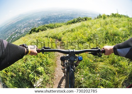 Photo of  View from the first person of a cyclist riding downhill from a high mountain in the background of a city in the distance