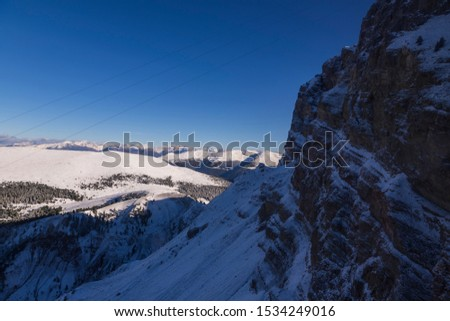 View from the gondola cabin to the snow-capped Seceda peaks in the Italian Dolomites.