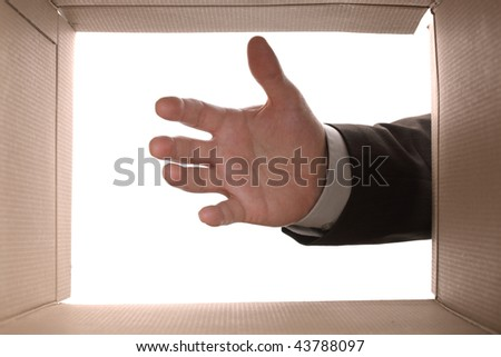 View from the inside of a cardboard box as a hand reaches in