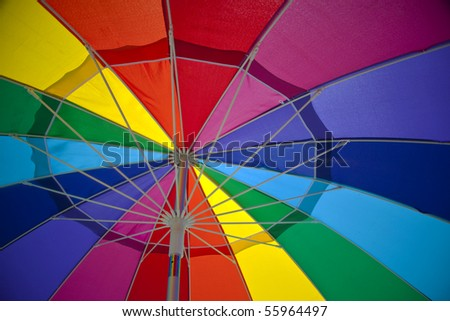view from the inside of a colorful beach umbrella