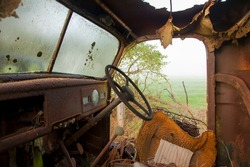 View from the inside of an abandoned rusty truck on a rural property with fog in the background.