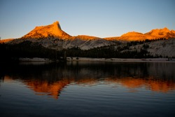 View from the John Muir Trail of Cathedral Peak at dusk with Alpine Glow reflecting in the still water of Cathedral Lake in Yosemite National Park in the Sierra Nevada Mountains in California