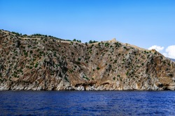 View from the Mediterranean Sea to the mountain with the ancient stone wall of the Alanya Castle on the peak (Turkey). Desert rock with a medieval fortress in the middle of blue water