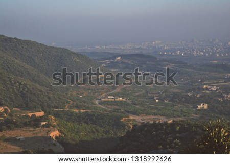 view from the mountain shah alla ditta islamabad, a beautiful heart warming view  the un developed part of the city  and the hills around the hills and mountains covered in lush green trees and gras   Foto d'archivio ©