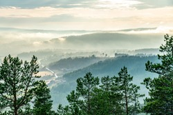 View from the mountain top over foggy Scandinavian mountains with wild pine tree forest, the village, mountain ridges, summer day with heavy dramatic clouds, North Sweden