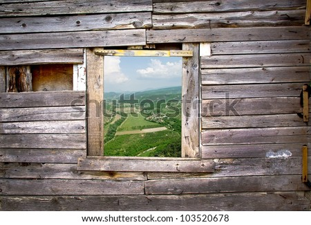 View from the old window - wooden frame of rural landscape. Window on the wooden wall with a farmland view. Countryside with green fields - view through the window on the wooden background.