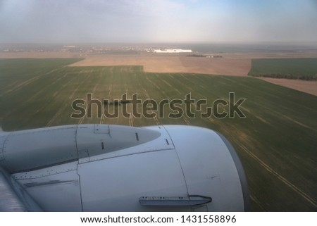 View from the plane window to the trees and meadows. Tourist route to warm countries. The theme of the travel agency. Stock photos