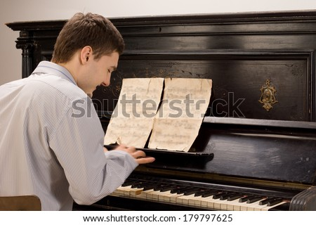 View from the rear of a young man smiling as he plays the piano using an old vintage music score on an upright wooden piano