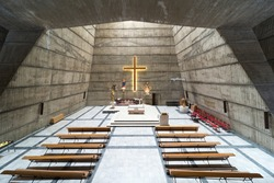 View from the rear of the seating area towards the altar and illuminated crucifix.Completed in 1969, in the brutalist Socialist style. this is the only Catholic church in Montenegro's capital city.