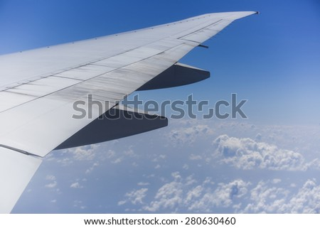 View from the right side of an aircraft of the wing, the plane is ready to land. It is a sunny day with a clear blue sky with clouds beneath it.