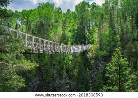View from the Rimouski river on the highest suspended footbridge in Quebec, 63 meters high and 99 meters long, located in Canyon des Portes de l'Enfer (Hell's gate Canyon) in Quebec, Canada Photo stock ©