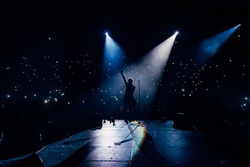 View from the stage stadium. Vocalist of a popular pop band on the background of the flashlights  of phones during a concert. Fans switch on lights on smart phones on tribunes. Crowd waving cellphones