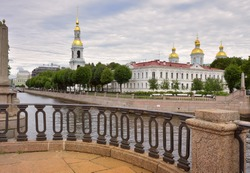 View from the Staro-Nikolsky bridge. Parapet of the Kryukov canal embankment, St. Nicholas Sea Cathedral with a bell tower and blue walls in the Russian Baroque style. Architecture of the XVIII