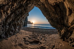 view from the stone cave on the sunset, sea and the beach, the volcanic rock of the cave is lit by the warm setting sun. volcanic basalt as in Iceland. Beauty world, nature and outdoors travel concept
