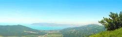 View from the summer green mountains Markotkh range to the Black Sea coast, bay, panoramic view. Rossia, Tsemesskaya Bay, Novorossiysk, Kabardinka
