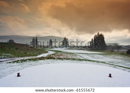 View from the tee of a golf course in Scotland on a snowy winter morning, with dramatic cloudy sky overhead.