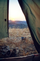 View from the tent: hiking shoes and tea cups against the backdrop of the mountains