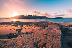 View from the tidal island of Grand Be to the city of Saint Malo and flooded path causeway at high tide at sunrise. Saint-Malo is famous city of Privateers is known as city corsaire, Brittany, France.