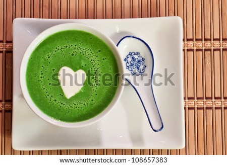 view from the top of a bowl of chilled sweet pea soup garnished with a heart shaped cream drop in the middle