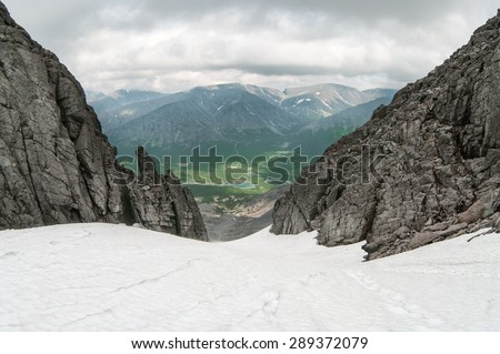 View from the top of snowy mountain pass at valley, summer season, Khibiny mountains in Russia #289372079