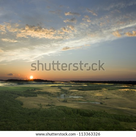 View from the top of the mountain. Colorful sunset. Blue sky and white clouds. Green field and summer forest. Beauty landscape