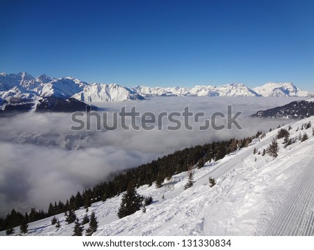 View from the top of the Swiss Alps looking down at a cloudy valley.