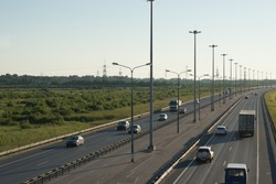 View from the top to a large highway with lanterns and a dividing strip, cars go in different directions
