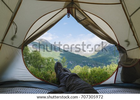 View from the tourist tent to the mountains. Guy in the boots lies on the rug #707305972