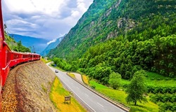 View from the train window on the mountain road. Mountain road view. Mountain train travel. Mountain scene