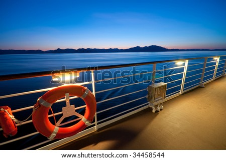 View from the upper deck of a cruise ship sailing in Alaska at dusk. - stock photo