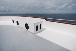 View from the upper deck of a safari boat with a rectangular box bench with three round holes from the air conditioning system, lit by the hot summer sun, with a seascape in a defocused background