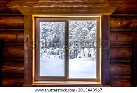 View from the window of the hut on the winter snow forest. Winter window. Window in winter snow. Winter window view