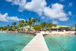 View from the wooden pier to the picturesque island of Martinique in the French Antilles. Relax in Martinique in sunny weather among palm trees, clear turquoise water and clean sand.