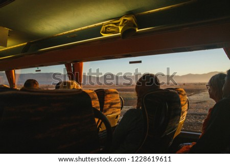 View from touristic bus on sunrise in mountains. Undefinied tourists looking to amazing landscape #1228619611