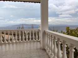 View from traditional Greek architecture white terrace balcony with balusters on stormy epic cloudscape and Aegean sea. Summer scenic view from country house near Athens, Greece