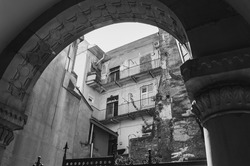 View from under the old church arch to the courtyard with a modern apartment building. Black and white photo of architecture.