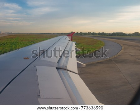 View from window seat, airplane landing on runway  then turn right into taxiway  to the terminal airport with green grass and blue sky background.