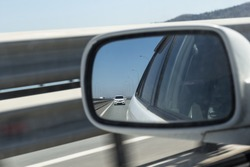View in the side mirror of the car. Another car goes to overtake