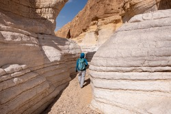 View inside a dry wadi Daras in a remote desert of the Northern Negev. Impressive white walls of a narrow winding canyon. Female hiker on a hiking trail in a heart of the desert. Nature reserve.