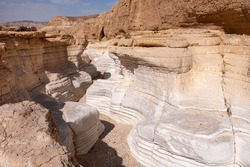 View inside a dry wadi Daras in a remote desert of the Northern Negev. Impressive white walls of a narrow winding canyon. Hiking trail in a heart of the desert. Nature reserve.