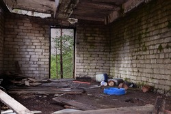View inside a ruined and abandoned brick building. Garbage and the remains of a collapsed roof are lying around.