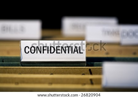 "view inside filing cabinet with brown file folders, green folder with ""confidential"" label in focus"