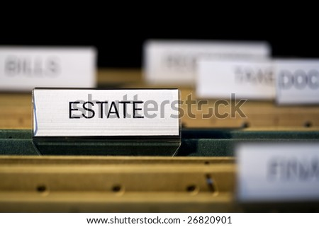 """view inside filing cabinet with brown file folders, green folder with """"estate"""" label in focus"""