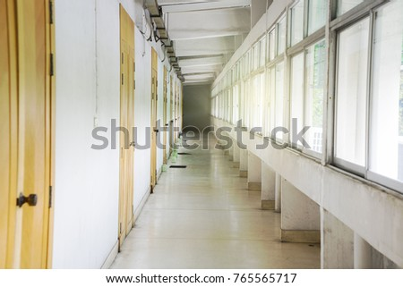 View inside the entrance to the terrace corridor in front of room, old school or apartment building, dead end long and narrow walkway and glass window with early morning orange shine.  #765565717