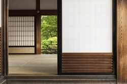 View into a japanese room with open shoji door and green garden in the background.