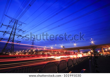 View long exposure of cars passing through  of the highway and transmission tower