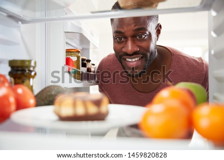 View Looking Out From Inside Of Refrigerator As Man Opens Door And Reaches For Unhealthy Donut #1459820828
