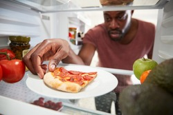 View Looking Out From Inside Of Refrigerator As Man Opens Door For Leftover Takeaway Pizza Slice